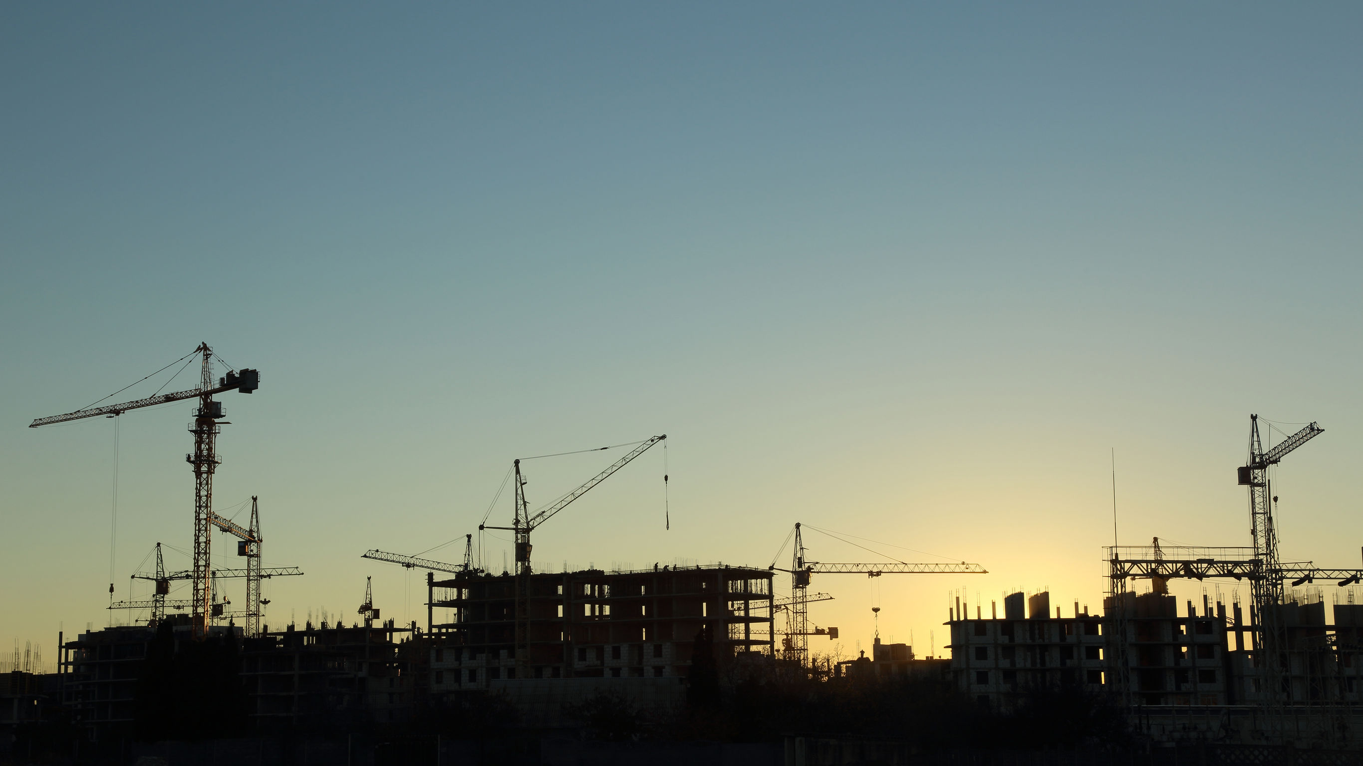 34309962 - silhouettes of construction  and power lines at sunset